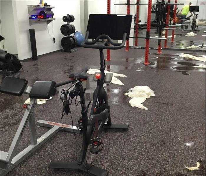 Gym with workout equipment and standing water on the floor