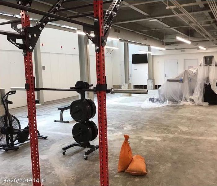 Gym with workout equipment, some wrapped in plastic, floor exposed