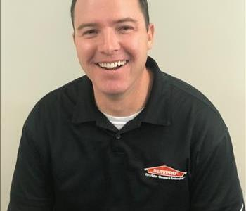 Male Employee Smiling in front of white wall.