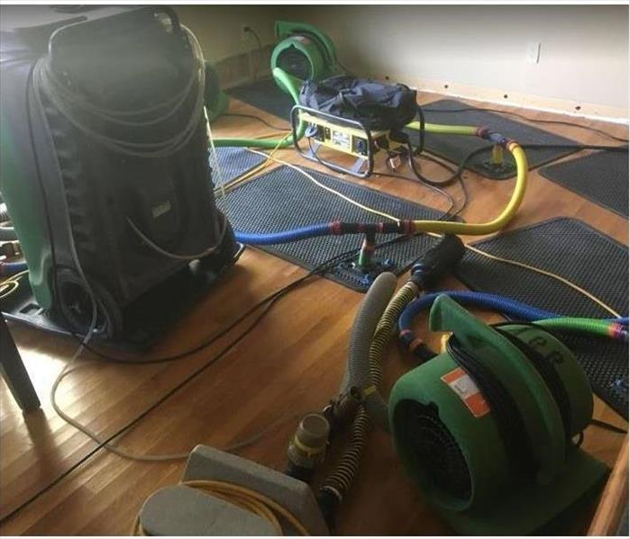 SERVPRO drying equipment and drying mats being used on water damaged hardwood