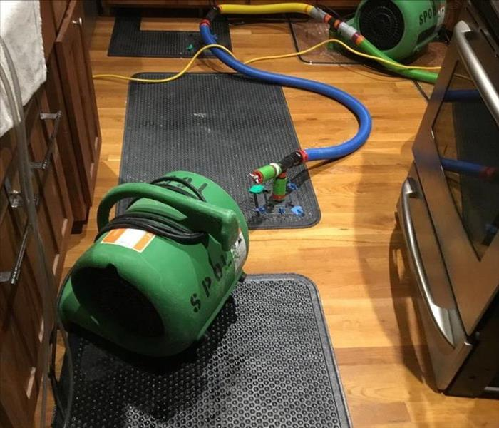 air movers working with black drying mats on a wooden floor in a kitchen