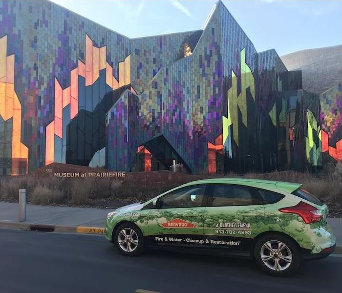 Green SERVPRO car sitting on the road in front of a museum with multi colored windows