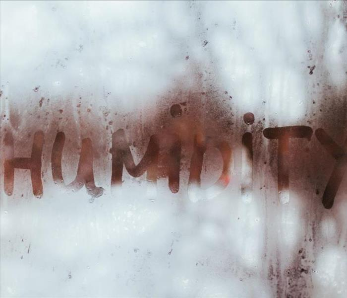 Water Droplets on a Window with the word Humidity