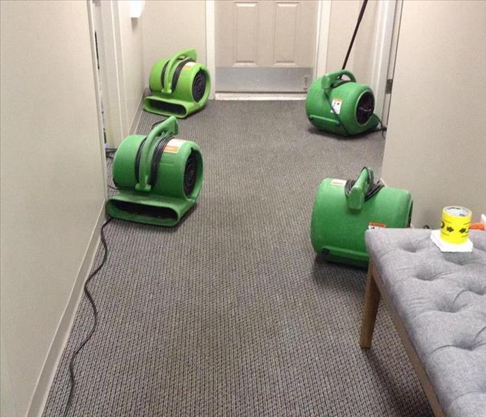 SERVPRO equipment on the floor of an office hallway.